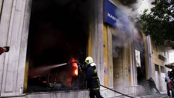 A firefighter tries to extinguish a fire at the branch of Marfin Egnatia Bank, where three people died, in central Athens, Wednesday, May 5, 2010