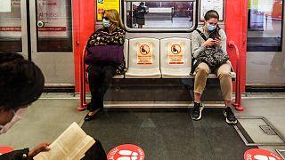 Des passagers dans le métro de Milan respectent la distanciation physique laissée par deux fauteuils vides