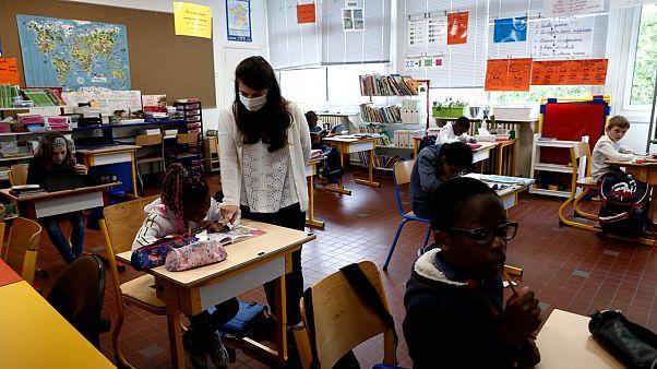 مدرسة رفقة أطفال وهي تحمل قناعا في مدرسة أساسية قريبة من باريس
