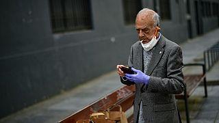 Un uomo con il viso parzialmente coperto da una mascherina, fuma una sigaretta a Pamplona (Spagna). 02/05/20
