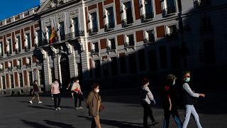 People wearing face masks to combat the spread of coronavirus continues walk at Sol square in Madrid, Spain,