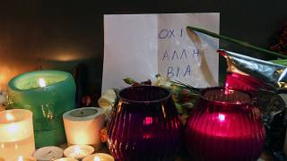 The sign behind the candles reads ''No more violence'' at the Marfin Egnatia Bank where three employees burnt to death in 2010