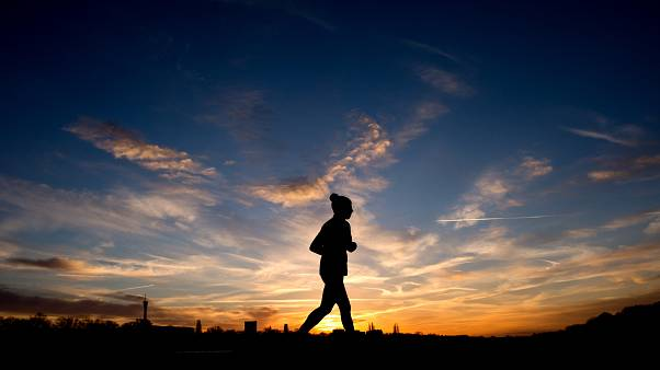 A jogger is silhouetted against the morning sky during sunrise in Hannover, northern Germany, Jan. 3, 2014. (AP Photo/dpa, Julian Stratenschulte)