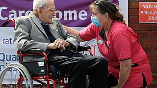 98-year-old care home resident Albert Rose talking to carer Jeanette on his birthday in Scunthorpe, UK on May 4, 2020, (Photo by Lindsey Parnaby / AFP)
