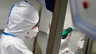 French lab scientist in hazmat gear inserting liquid in test tube manipulates potentially infected patient samples at Pasteur Institute in Paris, Thursday, Feb. 6, 2020.