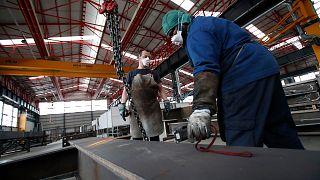 Operários de uma fábrica italiana trabalham de máscara devido à Covid-19