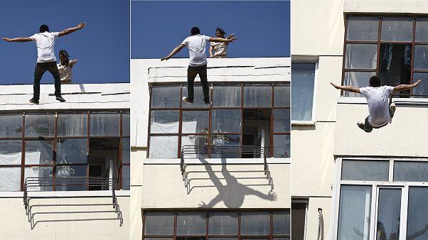 رجل يسقط من على سطح مبنى سكني