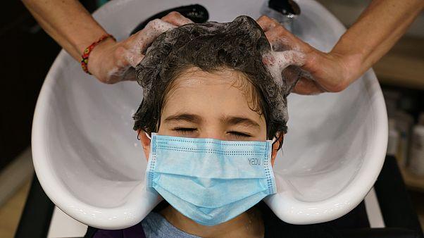 Une coiffeuse espagnole lave les cheveux d'une cliente dans son salon de Burgos le 4 mai 2020, pour la première fois depuis le début d'un confinement contre le Covid-19