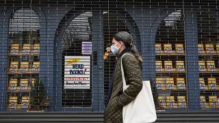"""A woman walks by the closed """"Books Are Magic"""" bookstore on May 5, 2020 in the Brooklyn borough of New York City. (Photo by Angela Weiss / AFP)"""