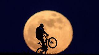 Kerékpáros a felkelő Hold előtt Salgótarján közelében 2020. május 7-én