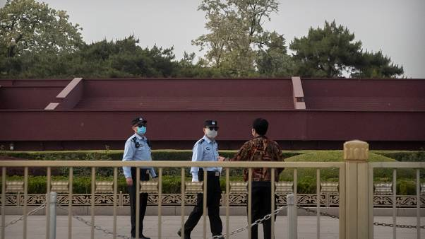 شرطيان صينيان يتحدثان إلى شخص قرب ساحة تياننمان في بيكين.