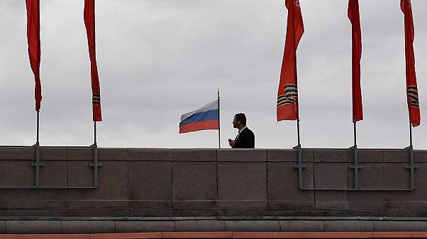 A man walks on a bridge past red banners devoted to the 75th anniversary of the victory over Nazi Germany during World War II, in downtown Moscow on May 9, 2020