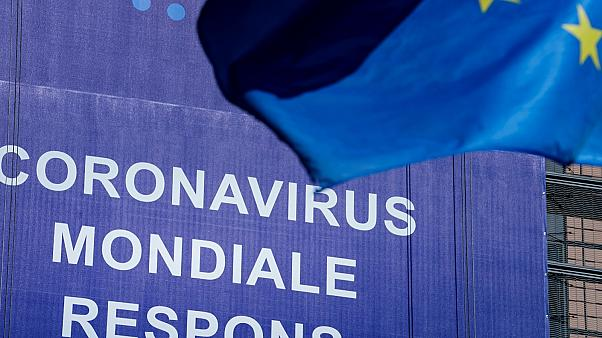 """An European Union (EU) flag flutters in front of a newly hung banner that reads """"Coronavirus Global Response"""" in front of The EU Commission building in Brussels. May 6, 2020"""