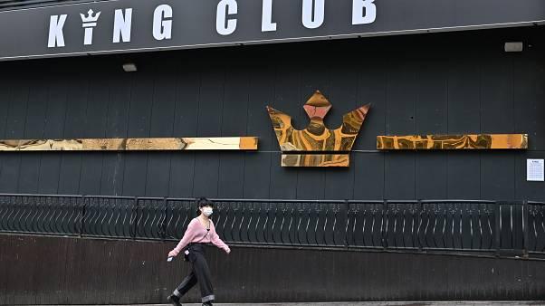 A woman wearing a face mask walks past a night club,on May 10, 2020. - South Korea