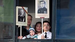 Ermakov's family who cannot go outside to celebrate Victory Day due to coronavirus hold portraits of their ancestors.