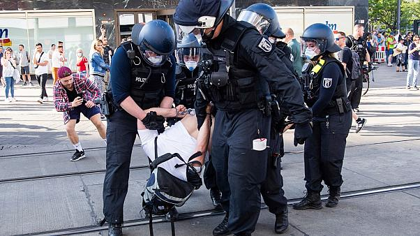 Police detain a protestor, during a demonstration on Alexanderplatz, in Berlin, Germany, Saturday, May 9, 2020.