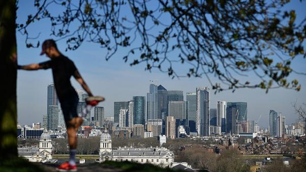 London's financial district Canary Wharf is seen as a man exercises in Greenwich Park