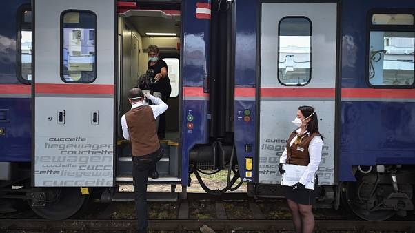 A woman is helped by conductor while boarding a train in Timisoara