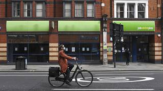 File photo: In this Thursday, April 30, 2020 photo, a woman wearing a mask to protect against coronavirus, rides a bicycle past a job centre in Shepherd's Bush, London.