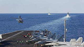 In this Tuesday, Nov. 19, 2019, photo made available by U.S. Navy, a helicopter lifts off of the aircraft carrier USS Abraham Lincoln as it transits the Strait of Hormuz.