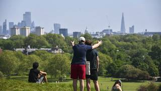 People enjoy the warm weather at Primrose Hill, as Britain faces its seventh week of lockdown due to the coronavirus outbreak, in London, Saturday, May 9, 2020.