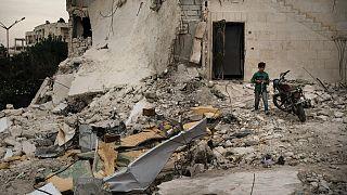 İdlib'de bir çocuk yıkılmış evlerden geriye kalanların arasında