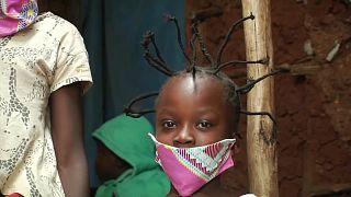 """طفلة في كينيا تحظى بتسريحة """"قصّة كورونا"""" في أحد الأحياء الفقيرة  بالعاصمة نيروبي"""