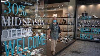 A woman wearing a mask to prevent the spread of the coronavirus exits a shoe store in central Athens, Monday, May 11, 2020, following the reopening of retail shops.