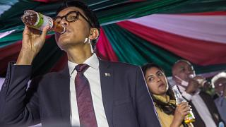 رئيس مدغشقر أندريه راجولينا  يتناول عينة من علاج كوفيد-19 العشبي المحلي