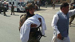 Afganistanlı asker Kabil'in batısında yaşanan hastane saldırısı sonrası bir bebeği taşıyor