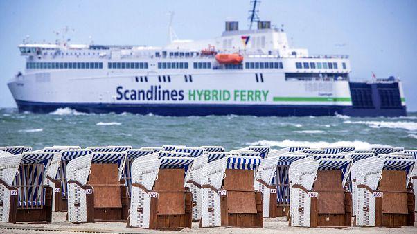 EIn Strand in Warnemünde bei Rostock: Im Hintergrund eine Fähre auf dem Weg nach Dänemark