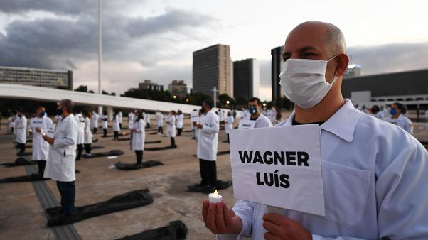 Brazilian nurses honour health workers who have died of the novel coronavirus COVID-19, during a demonstration in Brasilia.