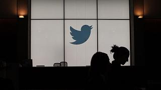 In this file photograph taken on August 14, 2019, employees walk past an illuminated Twitter logo as they leave the company's headquarters in San Francisco.
