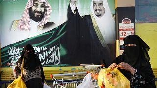 نساء تحملن أكياس التسوق أمام لافتة تظهر الملك السعودي سلمان وولي عهده الأمير محمد بن سلمان، خارج مركز تجاري في جدة.