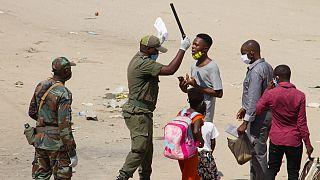 Um agente de autoridade interpela um jovem no distrito de Kifangondo, em Luanda