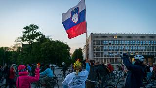 A man holds a Slovenian flag