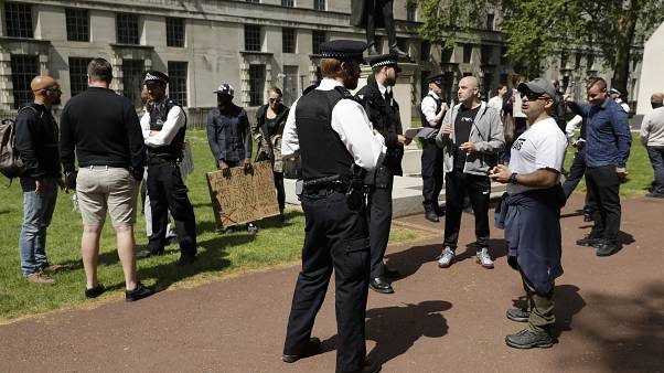 Police officers speak to people taking part in a coronavirus anti-lockdown, anti-vaccine, anti-5G and pro-freedom protest in London on May 2, 2020.