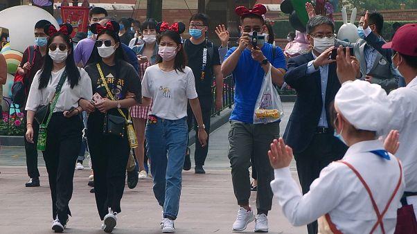 زائرون يرتدون أقنعة يدخلون حديقة ديزني في شنغهاي الذي أعاد فتح أبوابه - 2020/05/11