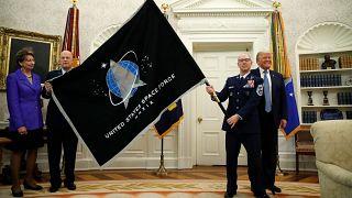 ضباط من وزارة الدفاع الأمريكية يعرضون علم قوة الفضاء الجديد على الرئيس الأمريكي في البيت الابيض