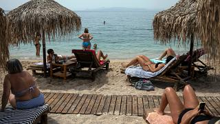 Swimmers enjoy the sea and the sun at Alimos beach, near Athens
