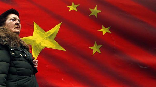 Szerb nő sétál egy kínai zászló előtt Belgrádban 2019-ben