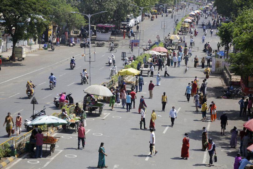 Los indios se agolpan en la carretera para ir de compras durante la relajación en el encierro para frenar la propagación del coronavirus en Ahmedabad, India, el domingo 17 de mayo de 2020.