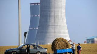 A pictureshows people transporting a bundle of straw close to the construction site of the first Belarus' nuclear power plant outside the town of Ostrovets