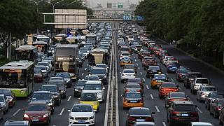 Cars are seen on a road in Beijing on May 12, 2020 (Photo by GREG BAKER / AFP)