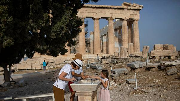 Visitors wash their hands in front of ancient Parthenon temple at the Acropolis hill of Athens, on Monday, May 18, 2020.