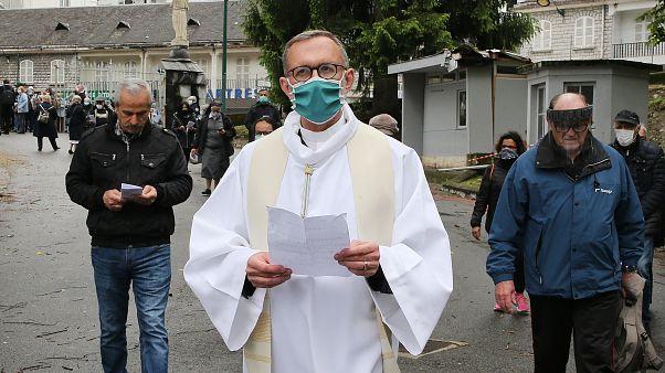 Olivier Ribadeau Dumas accompanies the first pilgrims into the Lourdes Roman Catholic sanctuary, in southwestern France, Saturday, May 16, 2020