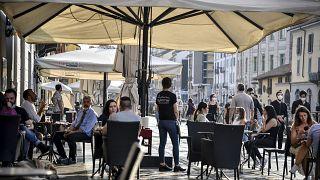 Personas sentadas en un café en Milán, Italia, el lunes 18 de mayo de 2020.