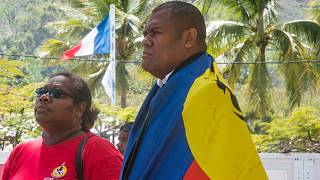 A man and a woman line up to cast their votes at a polling station in Nouméa, New Caledonia, as part of the independence referendum - November 4, 2018