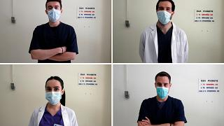 Nikolaos Katsanakis, top left, Ilias Sinanidis, top right, Anna Karagiannakou, bottom left, and Konstantinos Koufatzidis pose at the entrance of the COVID-19 Clinic at Sotiria