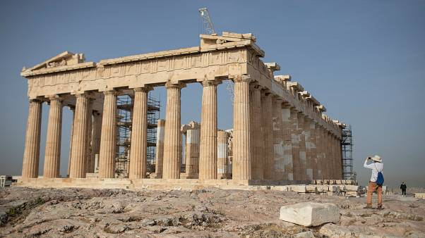 A man takes a picture next the ancient Parthenon temple at the Acropolis hill of Athens, on Monday, May 18, 2020
